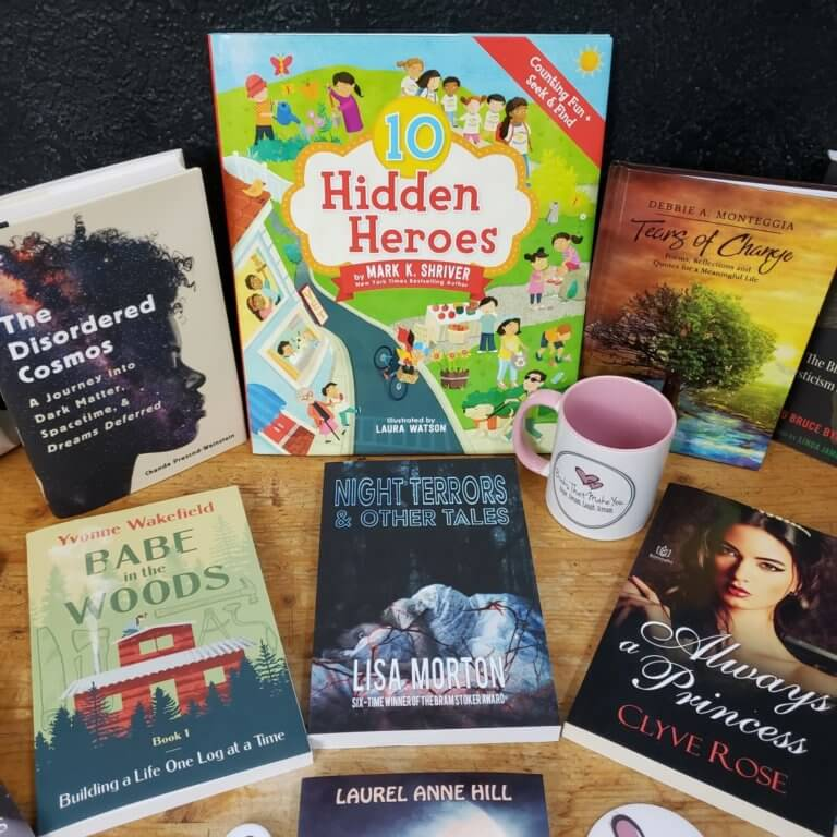 Six books and a coffee mug from Books That Make You arranged on a table. Prizes for The BookFest giveaway.