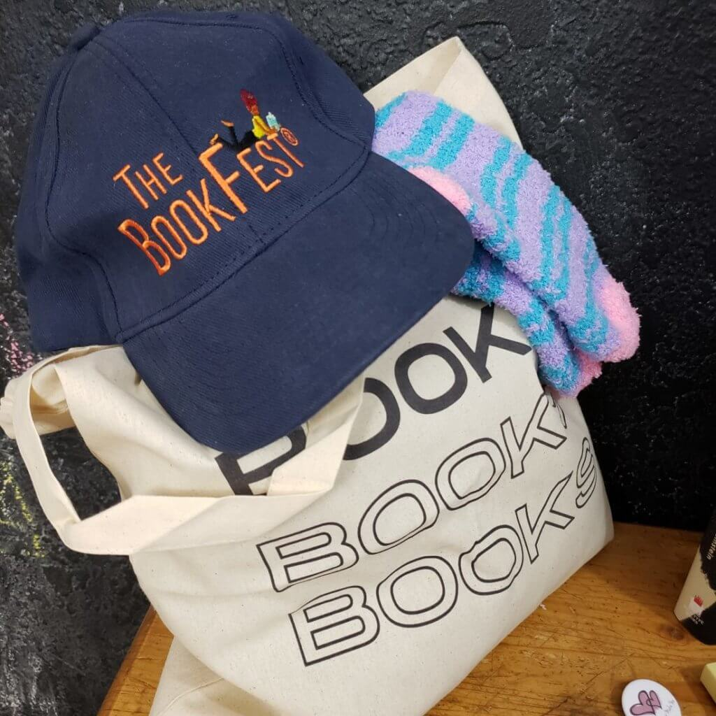 """Book bag that says """"Books."""" a pair of pink and blue socks, and a baseball hat that says """"The BookFest"""""""